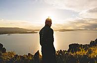 Peru, Amantani Island, back view of man enjoying sunset from Pachamama peak - GEMF000882