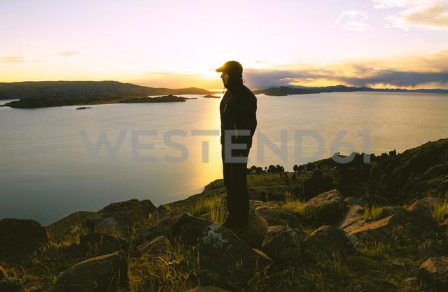 Peru, Amantani Island, man enjoying sunset from Pachamama peak - GEMF000885