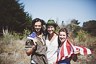 Portrait of three smiling hippies with US flag in the nature - GIOF000899