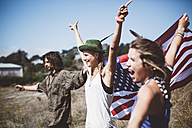 Three cheering hippies with US flag in the nature - GIOF000908