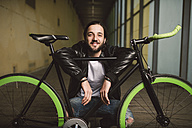 Smiling young man with fixie bike - RAEF001110