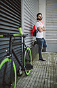 Young man leaning against wall next to fixie bike - RAEF001131