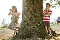 Little boy and girl playing with tin can phone in nature - ZOCF000115
