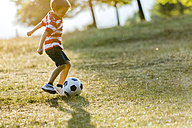 Little boy playing soccer on a meadow - ZOCF000121