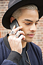 Portrait of young man wearing rings and hat telephoning with smartphone - CHAF001658