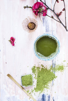 Matcha tea in bowl, with match powder, spoon and chasen and pink flowers - SBDF002863