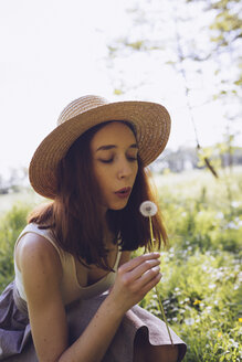 Young woman on a meadow blowing blowball - GIOF000914