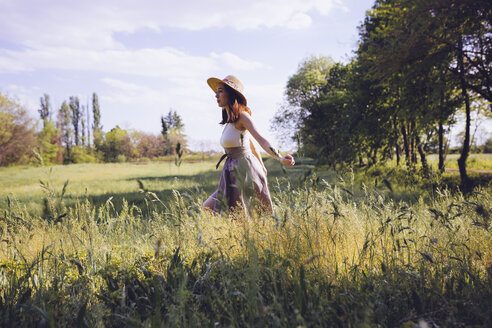 Young woman walking on a meadow in spring - GIOF000920