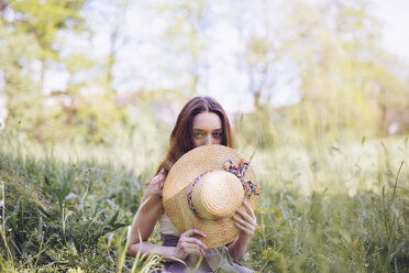 Young woman crouching on a meadow in spring - GIOF000923