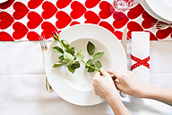 Hands putting rose on dish at laid table - LVF004823