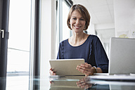 Portrait of smiling businesswoman with digital tablet at office desk - RBF004420