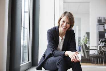 Smiling businesswoman sitting at the window - RBF004432