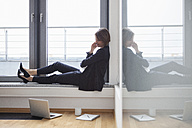 Smiling businesswoman sitting at the window looking at laptop - RBF004435
