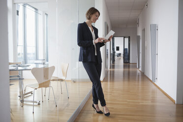 Businesswoman using digital tablet in office hall - RBF004444