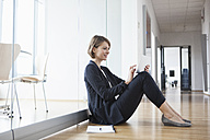 Businesswoman sitting on office floor using digital tablet - RBF004450