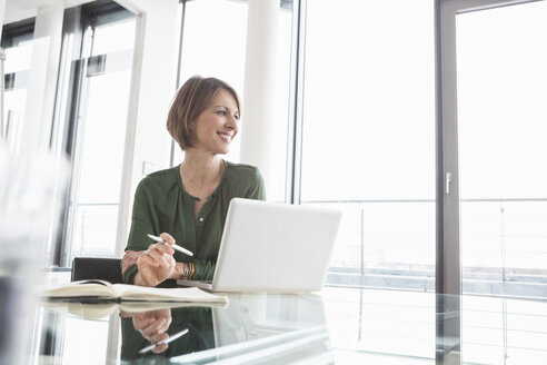 Smiling businesswoman at office desk - RBF004468