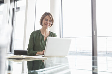 Portrait of smiling businesswoman working on laptop at office desk - RBF004471