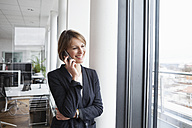 Smiling businesswoman on cell phone at the window - RBF004474