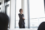 Smiling businesswoman on cell phone at the window - RBF004477