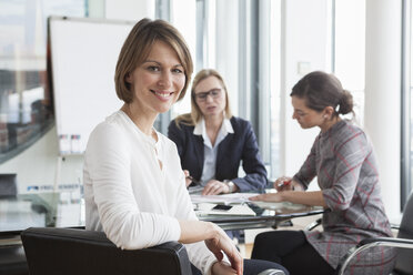 Portrait of smiling businesswoman in a meeting - RBF004492