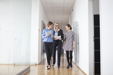 Three businesswomen walking and talking in office hall - RBF004498