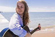 Smiling young woman with guitar at seaside - BOYF000287