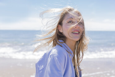 Portrait of smiling young woman with blowing hair at seaside - BOYF000290