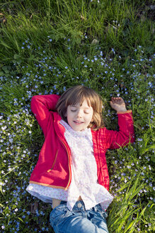 Portrait of little girl with eyes closed relaxing on a meadow - LVF004826