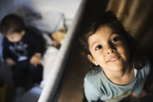 Portrait of little girl looking up to camera while her little brother playing in the background - JASF000708
