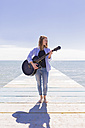 Young woman with guitar on jetty - BOYF000330