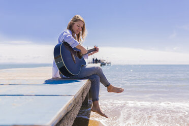 Young woman with guitar sitting on jetty - BOYF000333