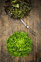 Two different leaf salads and pocket knife on wood - LVF004843