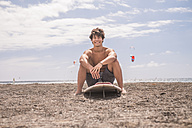 Portrait of smiling young man sitting on his surfboard on the beach - SIPF000411