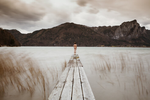 Austria, Lake Mondsee, Rear view of nude man standing on pier - WV000752