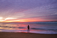 USA, California, Marina State Beach, Rear view of nude man standing at beach, afterglow - WV000755
