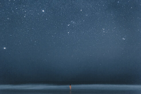 Rear view of nude man standing in water, looking to stars at night - WV000758