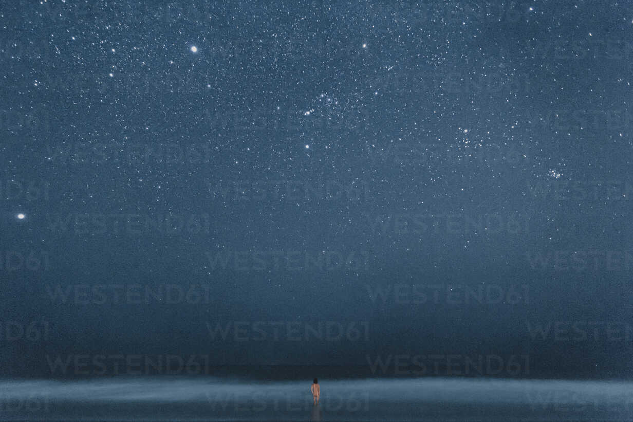 Rear view of nude man standing in water, looking to stars at night - WV000758 - Valentin Weinhäupl/Westend61