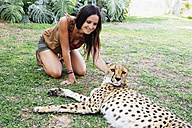 Namibia, Kamanjab, tourist petting a tame cheetah - GEMF000891