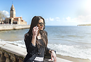 Young beautiful woman talking on phone on the beach - MGOF001809