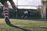 Legs of a footnball player kicking a ball in front of a goal with a goalkeeper - ABZF000448