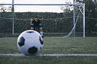 Unfocused football in front of a goal with a goalkeeper - ABZF000475