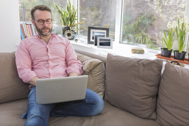 Mature man sitting on couch using laptop - BOYF000339