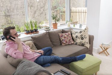 Mature man sitting on couch talking on the phone - BOYF000345