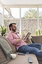 Mature man sitting on couch using digital tablet - BOYF000348