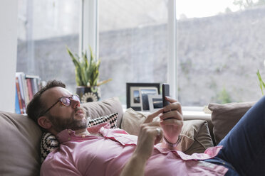 Mature mna lying on couch checking messages on smart phone - BOYF000354