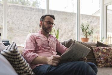 Mature man sitting on couch reading newspaper - BOYF000357