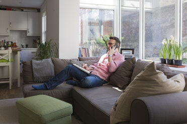 Mature man sitting on couch talking on the phone - BOYF000360
