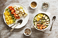 Smoothie bowl with different fruits, mango, papaya, kiwi, banana and pear and toppings, lineseeds, sunflower-seeds and nuts - EVGF002931
