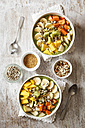 Smoothie bowl with different fruits, mango, papaya, kiwi, banana and pear and toppings, lineseeds, sunflower-seeds and nuts - EVGF002934