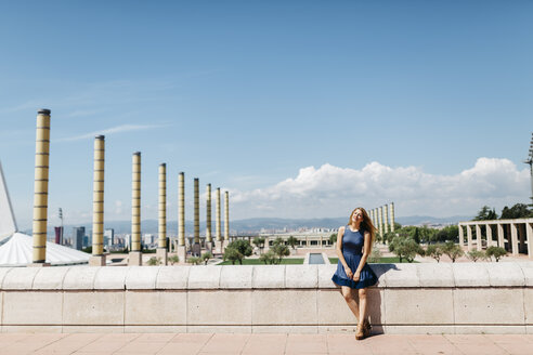 Spain, Barcelona, smiling woman relaxing at sunlight - JRFF000604
